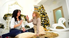 Charming friends friendly joke with each other and laugh, sit on floor on background of fireplace and Christmas tree in. Funny and lovely girls share secrets and stock footage