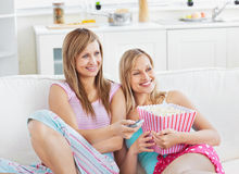 Charming friends watching tv eating popcorn Royalty Free Stock Photography