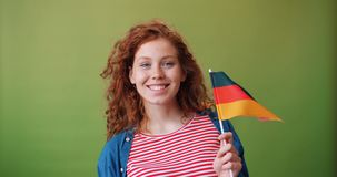 Charming German teenage girl holding national flag of Germany smiling. Standing on green background enjoying patriotic feelings. Youth and countries concept stock footage
