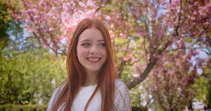 Charming ginger female student in white blouse posing gracefully into camera in pink floral garden. Charming ginger female student in white blouse posing stock video footage
