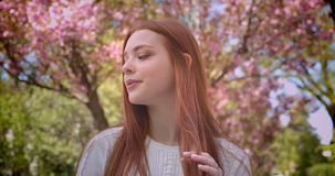 Charming ginger female student in white blouse watching dreamily leftwards and into camera in pink floral garden. Charming ginger female student in white blouse stock video footage