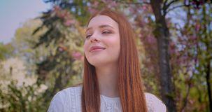 Charming ginger female student in white blouse watching dreamily at pink floral garden. Charming ginger female student in white blouse watching dreamily at pink stock video footage