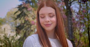 Charming ginger girl in white blouse poses into camera changing poses in pink floral garden. Charming ginger girl in white blouse poses into camera changing stock video footage