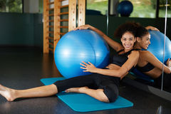 Charming girl with afro hair relaxing after Pilates exercise at fitness center Royalty Free Stock Photo