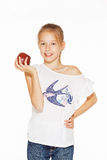 Charming girl with an apple. Cute little girl holding red fresh apple Stock Image