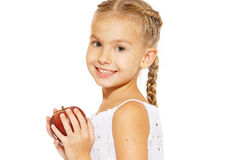 Charming girl with an apple. Cute little girl in a white dress bites red fresh apple Stock Photography