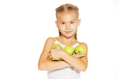Charming girl with an apple. Cute little girl in a white dress bites red fresh apple Royalty Free Stock Images