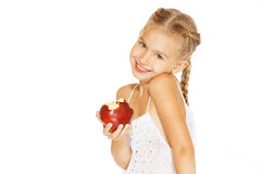 Charming girl with an apple. Cute little girl in a white dress bites red fresh apple Stock Photo