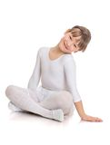 Charming girl athlete sits on the floor folded in Stock Photography