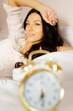 Charming girl awaking in nightclothes with clock Royalty Free Stock Image