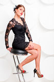 Charming girl in a black dress on a chair Stock Image