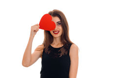 Charming girl in black dress smiles and keeps the ball red heart near your eyes Stock Photography