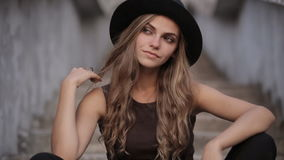 Charming girl in a black hat poses for the camera stock footage