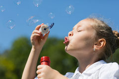 Charming girl blowing soap bubbles Royalty Free Stock Image