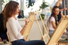 Charming girl with brown curly hair dressed in white blouse creates a picture at the easel holding the brush in her stock images