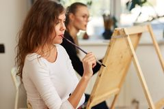 Charming girl with brown curly hair dressed in white blouse creates a picture at the easel holding the brush in her stock image