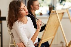 Charming girl with brown curly hair dressed in white blouse creates a picture at the easel holding the brush in her stock photo