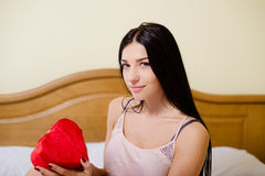 Charming girl in camisole holding red heart shaped. Picture of charming girl in silk camisole holding red heart shaped gift box. Young woman with long hair royalty free stock images