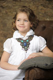 Charming girl child in a white blouse with a beautiful necklace. With a stone around his neck Stock Photos