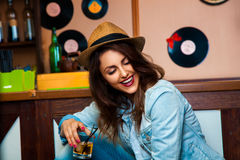 Charming girl with cocktail in hand laughing at the bar counter Stock Images