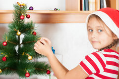 Charming  girl decorates  spruce Royalty Free Stock Photos