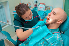Charming girl dentist checks the teeth of her patient Stock Image