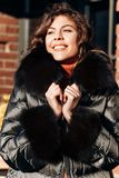 Charming girl dressed in black down jacket with fur poses in the street stock images