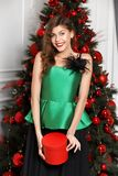 Charming girl dressed in a stylish green silk top, black full skirt poses next to the New Year tree royalty free stock photo