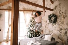 Charming girl dressed in white sweater and pants jumps on the bed with gray blanket and white pillows in a cozy stock image