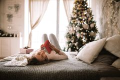 Charming girl dressed in white sweater and pants reads a book liying on the bed with gray blanket, white pillows and a stock photos