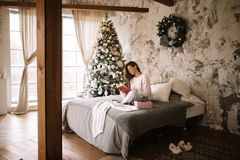 Charming girl dressed in white sweater and pants reads a book sitting on the bed with gray blanket, white pillows and a royalty free stock images