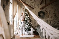 Charming girl dressed in white sweater and pants stands next to the New Year tree in front of the window and stretches royalty free stock image