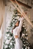 Charming girl dressed in white sweater and pants stands next to the New Year tree in front of the window and stretches royalty free stock photos