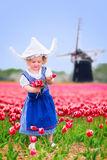 Charming girl in Dutch costume in tulips field with windmill. Adorable curly toddler girl wearing Dutch traditional national costume dress and hat playing in a Royalty Free Stock Images