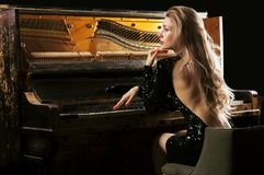 The charming girl in an evening dress plays the old German piano. Back view stock photo