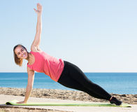 Charming girl exercising on exercise mat outdoor Stock Photos