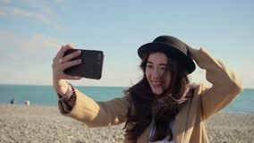 Charming girl is filming video of herself by mobile camera in sunny beach stock footage