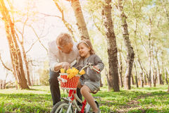 Charming girl with grandfather in park. Elderly men teaching little girl to tide bicycle in spring park Stock Photo