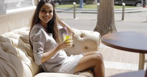 Charming girl having refreshing drink in cafe royalty free stock image