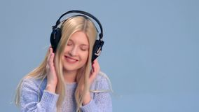 Charming girl with headphones listening to music stock video