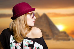 Charming girl in hipster glasses on Egypt pyramid. Picture of pretty woman in big glasses and pot hat with naked shoulder. Charming girl on Egypt pyramid blurred Stock Photo