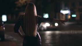 Charming girl hitchhiking on town street at night stock video footage