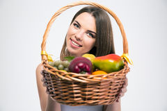 Charming girl holding basket with fruits. Portrait of a smiling charming girl holding basket with fruits isolated on a white background Stock Images