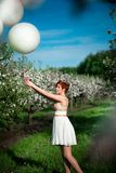 Charming girl holding white balloons looking sadly at them stock photography