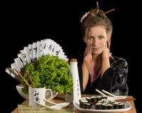 Charming girl in kimono eating sushi Stock Image