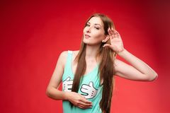 Charming girl listening to gossips. Studio portrait of beautiful caucasian. Studio portrait of curious brunette girl in multicolored top listening to the news or stock images