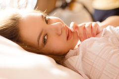 Charming girl lying in bed on blurred morning Royalty Free Stock Photo