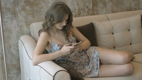 Charming girl in the nightgown sitting on the couch with the mobile phone stock footage