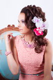 Charming girl in a pink dress and with flowers in her head. Portrait of curly brunette with purple make-up in pink dress with pink soutache technique decorations stock photo
