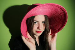 Charming girl with pink straw hat Stock Photos